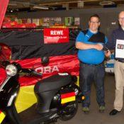 Torsten Nieuwenhuis (links) erhält von Marktleiter Achim Lütfring seinen neuen Motorroller