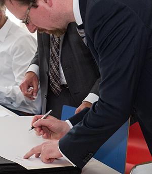 Alexander Lin unterschreibt seine Ernennungsurkunde